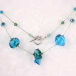 Turquoise and Green Lampwork Art Glass on Green Silk